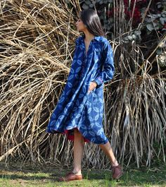 Our swing dress is crafted in 100% cotton fabric and the shibori pattern is achieved through tie and dye using natural Indigo dye. The design features a relaxed fit, long sleeves, classic collars, a front placket and a beautiful swingy bodice with on seam side pockets. Fine detailing in rani pink can be seen all across the hemline and sleeves. Belt it up for a dressier look.