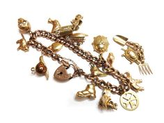 A gold hollow curb link charm bracelet. Sold for £370
