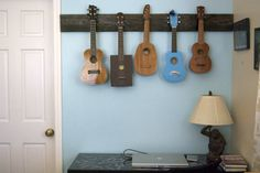 ukulele hanger - I thilnk we need one of these in the basement that holds ukes and guitars.