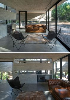This modern living room is minimally decorated with the floor-to-ceiling windows being the most important aspect in the room. A brown upholstered couch sits beside a black fireplace.