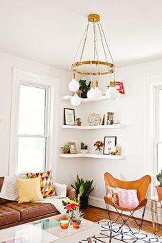 White room with open bookshelves in corner, modern light fixture, and feminine details