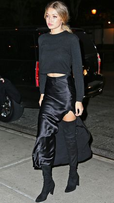 """GIGI HADID If there was such a thing as """"casual-glam,"""" it would look like Gigi's all-black ensemble here, which mixes low-key silhouettes with high-end fabrics (her cashmere Everlane sweater, satin slit skirt and thigh-high stretch leather Stuart Weitzman boots)."""