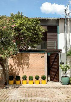 Entrada discreta. O sobrado de vila, com muro e portão altos, oferece privacidade aos moradores. À direita de quem entra, um grande armário acomodaferramentas, bicicletas, medidor de luz e cavalete de água.