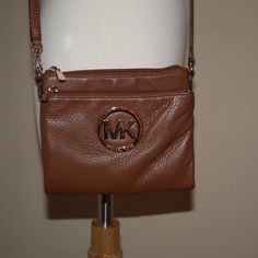 Michael Kors Crossbody Gold MK logo on the front pouch. Pocket with a zipper in the front, built in wallet in the middle with a coin pouch and built in card holders, and another bigger pocket with a zipper towards the back. Buttoned pocket on the very back outside. Leather strap. In GREAT condition. Goes with anything!!!! Michael Kors Bags Crossbody Bags