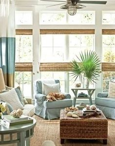 love the huge stripes drapes, rattan coffee table and soft blues
