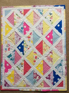 My very first quilt. Made 2 of them for my 2 granddaughters.My version of the Sophie car seat quilt from Moda Bake shop using half square triangles. I left off the extra border and quilted within them