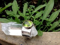 This exquisite ring features a stunning facetted Peridot with a 24-karat yellow gold setting on the front that holds the beautiful gemstone. The ring is handcrafted in 925 sterling silver and rhodium plated. Rhodium plating is used to increase the strength, durability, and bright look of silver. Rhodium (like gold) is a low tarnish metal and therefore remains bright and shiny under most environmental conditions. It enhances the beauty of silver and helps ensure the longest-lasting, most…