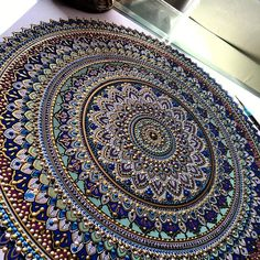UK based artist Asmahan A. Mosleh (aka murderandrose) creates intricate colorful mandala designs finished with pearls of color and gold leaf paint.