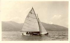 """J 74 auf dem Tegernsee. Aufnahme von J.Reitmayer von 1930. Man beachte den Leewärtigen Sitz der Besatzung für die dramatische Krängung und die Krachledernen des Steuermanns. Wohl die """"Amok"""" des Königlich bayrischen YC, evtl. handelt es sich dabei um Stipper XXI, dann Stipper-Pfalz, 1921 für den Potsdamer YC gebaut. Das Boot wird dann 1941 mit Christel zusammen im Drei-Seen-Wettkampf antrete"""