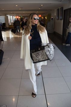 Elle Macpherson stands out in chic overcoat and white pants in Melbourne Airport | Daily Mail Online