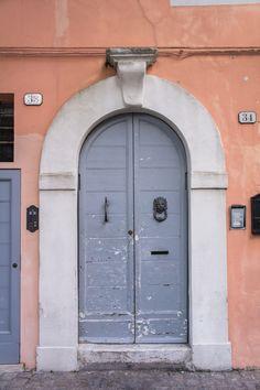 Grey door with lion head door knocker in Senigallia, Marche Region, Italy