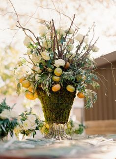 Dramatic centerpiece.  Green  moss, olive branches, citrus and white roses.
