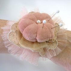 Pincushion bracelet. Idea - make pincushion, glue gathered and ruffled trim under and glue that onto a strip of ribbon (long enough to go round the wrist.)