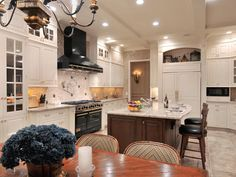 This warm, functional kitchen mixes shades of white, black and brown to soften the large space. The black metal range hood is adjacent to a sun-drenched seating area. The open kitchen layout overlooks the den and is well suited for entertaining.