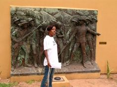 tour guide in front of a plaque in the Fort of Maputo