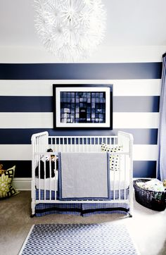 Blue and white striped nursery with white chandelier and patterned carpet