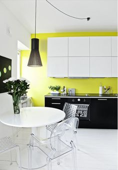 Contemporary cool in this mainly white kitchen with citrus coloured wall. Black base units and contemporary accessories give a nice edge to the scheme.