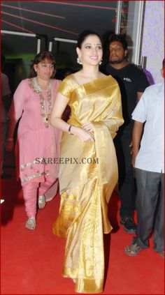 Heroine Tamanna Bhatia is looking georgeous in a silk saree with short sleeves silk blouse at the wedding reception of Brahmanandam son Gautham. The marria Designer Lehnga Choli, Lehenga Saree Design, Saree Blouse Designs, Saree Wearing Styles, Saree Styles, Indian Bridal Sarees, Indian Beauty Saree, Latest Silk Sarees, Golden Saree