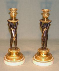 A pair of early 19th Century bronze and ormolu Candlesticks in the form of cherubs holding leaf moulded nozzles, raised on garland decorated platforms, ending on beaded decorated white marble plinth bases.   Circa: 1825