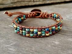 This leather wrap bracelet was made using rustic red, montana blue, seafoam green, jet black matte and brown jasper in a Picasso finish. I wove them between 2 rows of distressed natural brown leather. Fastens easily with a brass sunflower shank button. I absolutely love these