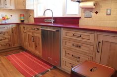 Custom cabinets by Creation Cabinetry crafted out of rustic knotty maple with a vibrant red quartz countertop for a home in Kutztown, Pennsylvania (Berks County).