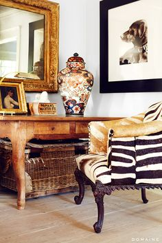 Eclectic corner with framed art and mirror and animal print chair
