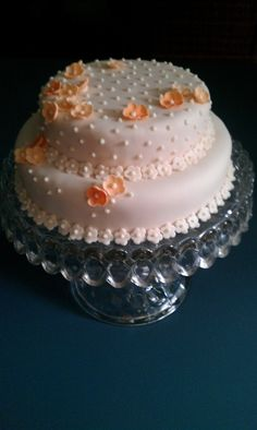 Two tier orange cake with orange cream cheese frosting. Covered in pale pink fondant with royal icing dots and gumpaste flowers