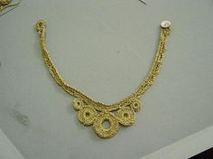 How to crochet an eye-catching necklace using sparkly gold yarn.