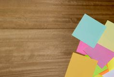 multi coloured note paper on a wooden background