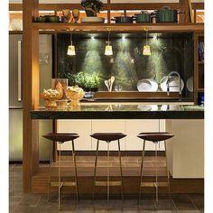 Apaixonada por essa cozinha americana com bancada alta iluminada por três pendentes. O mármore que reveste a bancada da cozinha e um espetáculo à parte.