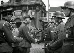 Charleroi, Belgium, April 1st 1944 .- Sturmbrigade Wallonien award ceremony. Degrelle awards the Iron Cross 1st Class to SS-Obersturmführer Marcel Lamproye (Chef 5. Panzerabwehrkompanie). To the  right: SS-Obersturmführer Marcel Bonniver (Chef 4. Sturmgewehrkompanie) and SS-Untersturmführer Jean-Marie Lantiez (Chef Nachrichtenzug). At Degrelle's left is Josef Sepp Dietrich.