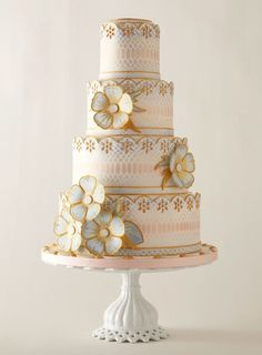Inspired by sexy snakeskin and glossy pearls, Kerry Vincent hand-stenciled a python pattern and topped it with borders reminiscent of embroidered English lace. Hand-painted fondant cake with gum-paste flowers, $25 per slice, Romantic Wedding Cakes by Kerry Vincent, Tulsa, OK