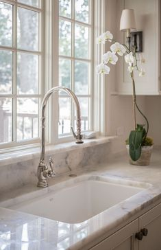 kitchens - farmhouse sink white kitchen cabinets black honed countertop polished nickel bridge faucet beadboard ceiling Sunny kitchen with lots