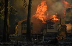 A firefighter battles flames of a burning home; Lower Lake, CA —Josh Edelson
