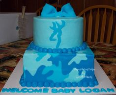 Blue Camo Baby Shower - cakes iced in home made buttercream. I hand piped the camo pattern onto the cake. The bow browning deer head are fondant. The colors of this cake look prettier in person, I had trouble capturing the colors for some reason. Camo Baby Cake, Camo Diaper Cake, Camo Cakes, Camo Baby Stuff, Deer Cakes, Baby Shower Cupcakes For Boy, Baby Shower Camo, Cupcakes For Boys, Camo Birthday