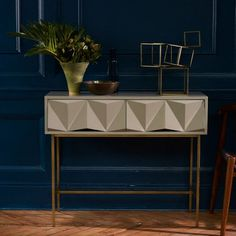 Gorgeously geometrical. With its strikingly modern drawer fronts hewn from powder-coated brushed metal and laid atop antique brass-finished legs, this Sculpted Geo Console's architectural shape is balanced by its soft color palette. ➤For more inspirational ideas take a look at: www.modernconsoletables.net #consoletables #homedecorideas #luxuryhomes