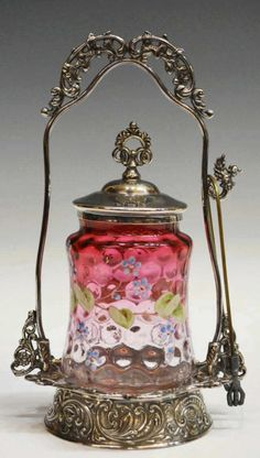 American Victorian pickle castor, the M.S. Benedict Mfg. Co., Syracuse, New York, the fancy foliated silver plate frame fitted with a cranberry to clear glass insert, thumbprint pattern on the body finely enameled with flowering branches and remnants of gilding, accompanied by pickle tongs with talon ends