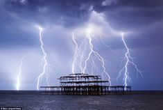 Lightning strikes the sea around the wreckage of Brighton's West Pier last night. Just hours later, the nearby beach would be inundated with people wanting to sunbathe