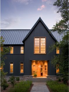Dark grey vertical siding and steel roof make this modern Farm House a must see. Paint color is Rock Bottom by Sherwin Williams.