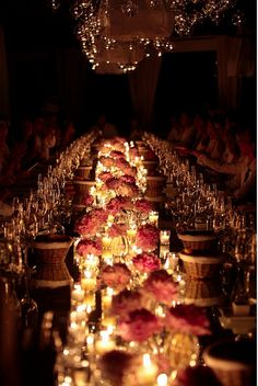 Clusters of single flower centerpieces with candle light line the middle of the reception tables. What an absolutely magical look!