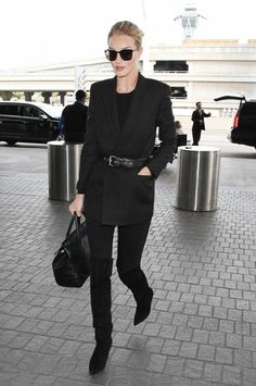 Rosie Huntington-Whiteley wears a black top, belted blazer, skinny  jeans, thigh-high boots, a satchel, and square sunglasses