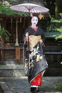 the maiko kimika in a black formal kimono + golden crane kanzashi