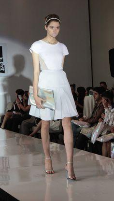 Playera con costados de mesh, falda con tablas en el centro, clutch oversize de vinil iridiscente