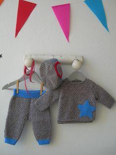 Jersey y pantalón para bebe hechos a punto fantasía en mezcla de 2 colores con aplicación estrella ganchillo. El pantalón tiene elásticos de color azul. Le combina el gorro gris con puntos azules.