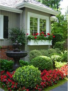 window box & flower bed with fountain. http://pinterest.com/intlhomeshow/.  I like the foundation plantings with a little color and window boxes.  Minus the fountain :)
