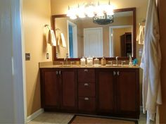 Bathroom Remodel: dark wood cabinets; cream colored stone countertops; jack and jill sinks; standalone framed mirror