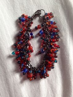 Chunky Clear and frosted red and dark blue beaded charm bracelet on black chain!   Price: £8  Warning: Please keep this bracelet dry at all times! Do not wear it in the shower or continuous water use!