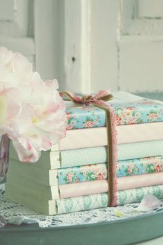 Wrap paper around the books  tie them together. This could be cute to put on our new shelves in the kitchen.