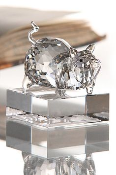 """Swarovski Zodiac Pig   $300.00 3 1/4""""   Item# 1047431          In China, the pig symbolizes carefree fun, good fortune and wealth. As the pig likes to be merry, others enjoy its company.  This fascinating animal is skillfully captured in faceted and unfaceted Silver Shade crystal with eyes that gleam in Moroda Tabac crystal. This stunning sculpture impresses with its authentic Asian design. The name of the Zodiac in English and Chinese seal script is engraved in the faceted clear…"""