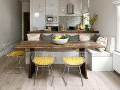 This dining area uses an interesting mix of pieces. The wooden dining table is surrounded on one side by a cushioned bench whilst on the other side sits a trio of Wire Chairs with brightly coloured leather cushions. This contrasting mix is undeniably effective!